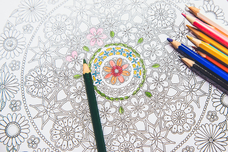 autocuidado: Anti-stress coloring book in the drawing process. Woman paints the razukrashki on the table are colored pencils, and tea, coffee