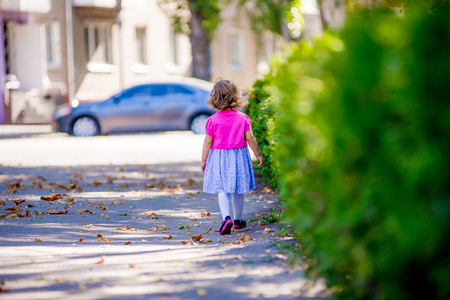 turn away: Little girl walking through the park looking for something turning back, girl tries to escape Stock Photo