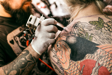 the process of creating a tattoo on the back of a girl. Professional tattoo. Carp Fish tattoo