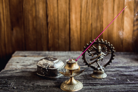 religious service: Incense in symbol and Beautiful Candlestick. Luxurious antique gold service. Spiritual religious Hindu concept. Eastern Still life on a blurred Background Stock Photo