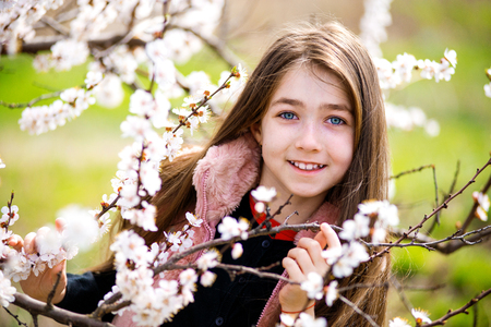 sincerely: Happy girl at blossoming garden in spring,  sincerely smiling Stock Photo