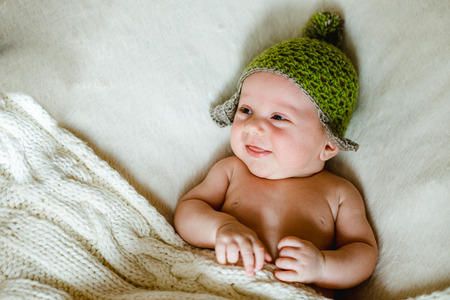 aliments droles: baby in a knitted cap is covered with a blanket and smiling