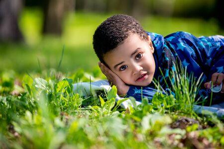 lindo niño feliz acostado en la hierba verde en primavera. muchacho negro