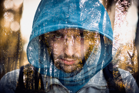 scheming: Close-up portrait of threatening gangster wearing a hood, representing the concept of danger. Close-up portrait of threatening gangster wearing a hood, representing the concept of danger