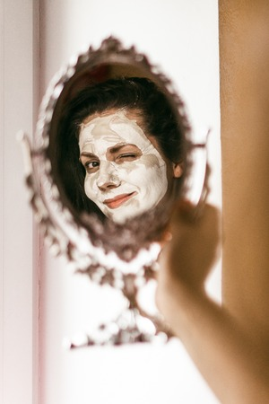 layer mask: Woman applying mask of clay skin on face looking in mirror. Woman applying mask of clay skin on face looking in mirror.