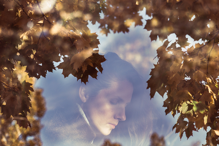 Double exposure portrait of attractive lady in the autumn leaves