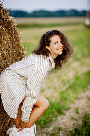 seductive women: Young beautiful woman on field with clothes off. In a shirt Stock Photo