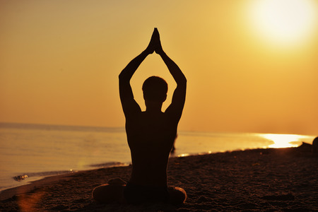A man in a lotus position doing yoga on the backdrop of the setting sun in the sea