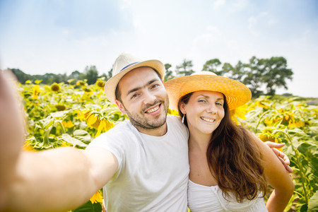 pics: young happy couple man and woman are in a field of sunflowers, make selfie pics, grimace and fun Stock Photo
