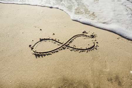infinity symbol written on Sand on the beach, ocean Imagens - 64385302
