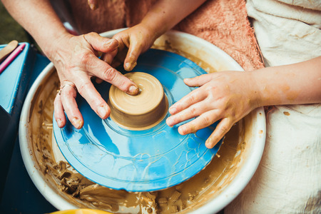 a child working on the potters wheel makes the shape of a new product
