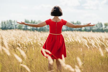 Meisje in een rode jurk lopen op het veld Stockfoto - 64386525
