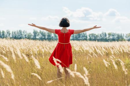 hombre rojo: chica en vestido rojo caminando en el campo. vista trasera Foto de archivo