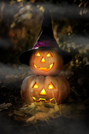 attribute: Grinning pumpkin lantern or jack-o-lantern is one of the symbols of Halloween. Halloween attribute. In the forest near the tree Stock Photo