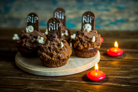 topper: Halloween cupcakes with tombstone cake topper and candle on an old wooden table