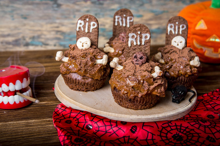 topper: Halloween cupcakes with tombstone cake topper on an old wooden table. Small cupcakes with gravestone with the inscription RIP