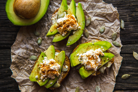 Sandwich with Avocado, black unleavened bread, mozzarella cheese, sprinkling spices and pumpkin seeds on over dark wooden textured background. Healthy eating theme.