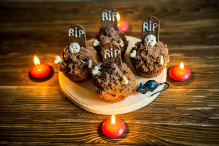 Halloween cupcakes with tombstone cake topper and candle on an old wooden table