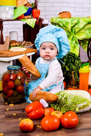 little girl in the cook clothes with loaf of bread in the kitchen Stock Photo