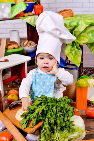 Pretty little girl in cook clothes found an idea on a kitchen Stock Photo