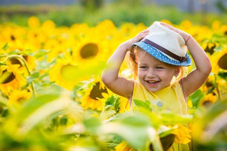 Happy little girl on the field of sunflowers in summer. beautiful little girl in sunflowers Standard-Bild
