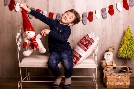 moulding: smiling happy boy waiting christmas and Santa sitting on a bed Stock Photo