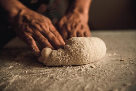 artisanal: woman knead the dough by hand on pies