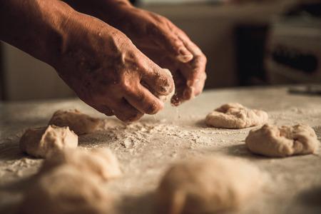 zelfgemaakte taarten van de deeg in de vrouwen handen. Het proces om deegdeeg met de hand te maken Stockfoto