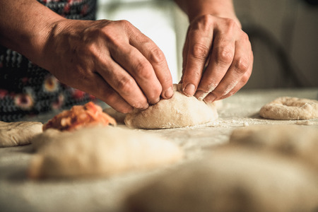 homemade cakes of the dough in the womens hands. The process of making pie dough by hand Stock Photo