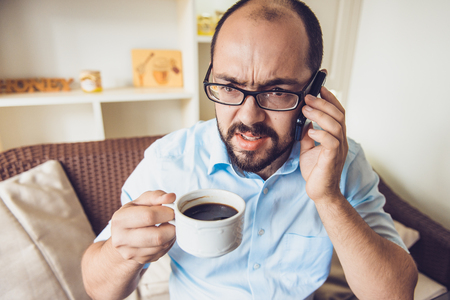 conversating: Angry businessman arguing on the phone and drinking coffee in a cafe Stock Photo