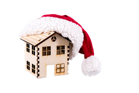 House wooden a cap of Santa Claus, isolated on white. Conceptual image. Stock Photo