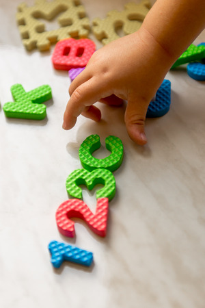unattached: Colorful foam puzzle letters and numbers in kids hands on a light table. Baby puts puzzle of letters and numbers. Close-up