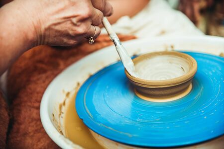 potters wheel: a child working on the potters wheel makes the shape of a new product