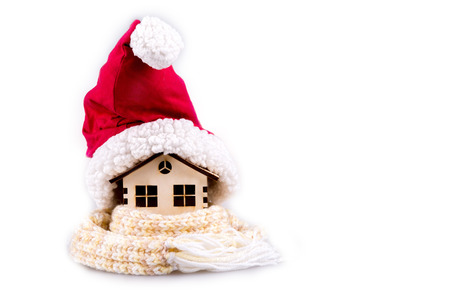 House wooden wrapped in a scarf, a cap of Santa Claus, isolated on white. Conceptual image.