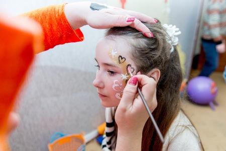 vrouw schilderen gezicht van het kind buitenshuis. baby gezicht schilderij