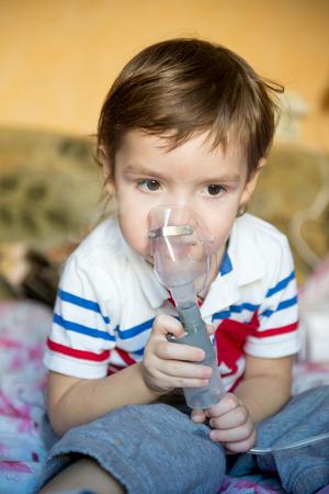 Schattige kleine jongen met astma of allergie problemen, verkoudheid, met behulp van inhaler thuis. Het gebruik van een vernevelaar kind