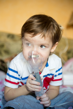Cute little boy with asthma problems or allergy, colds, using inhaler at home. The use of a nebulizer child