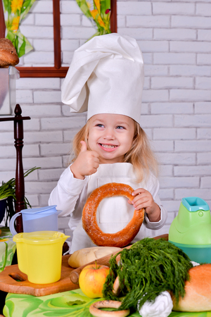 Little girl in a cook clothes with bagels in the hands of the kitchen. Stock Photo