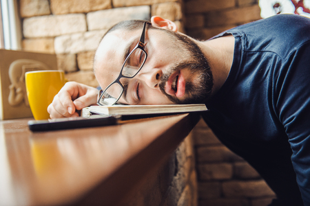 unshaven man in glasses tired, fell asleep at the table Stock Photo