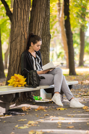 girl sitting in the park under a tree and reading a book Stock Photo