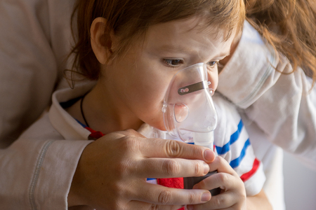 whooping: Young woman with son doing inhalation with a nebulizer at home. Mother of a young child making inhalation