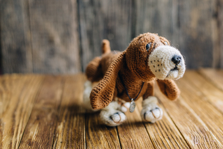 basset: Knitted dog Basset Hound isolated on wooden background. handmade toy