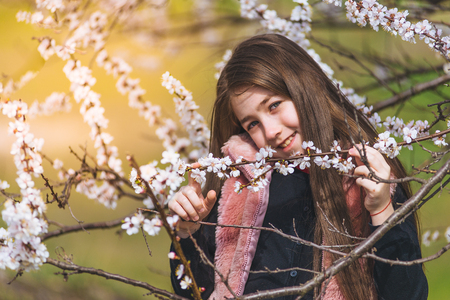 Happy girl at blossoming garden in spring, sincerely smiling Stock Photo