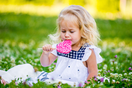 happy little girl eating a piece of candy on a stick in the form of heart. Valentines day concept Stock Photo