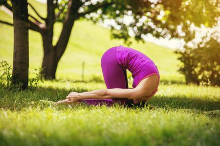 Sasangasana - pose de ioga de coelho. garota fazendo exercício sobre a natureza da ioga - pose de coelho Foto de archivo - 74106666