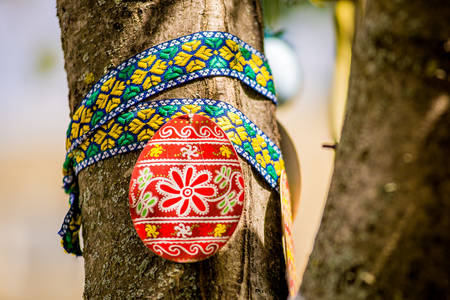 Several Easter colored eggs hanging on a tree branch color sunny spring day. Easter Stock Photo
