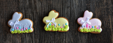 gingerbread: Easter holidays background - Easter bunnies cookies on a wooden background Stock Photo