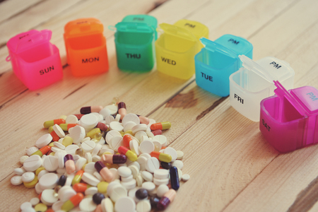 Pill box with variety of pills and supplement. A plastic weekly pill box. Daily pill box with medications and nutritional supplements. Stock Photo