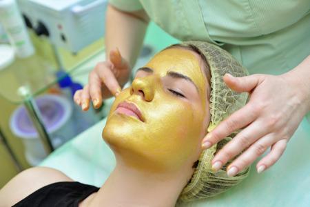 Gouden gezichtsmasker in de spa salon