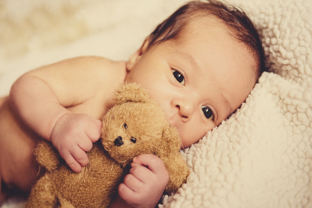 小さな子供のファリャの小さな子供がおもちゃでベビーベッドで眠りに落ちる、熊のぬいぐるみでベビーベッドで眠っているクマ 写真素材